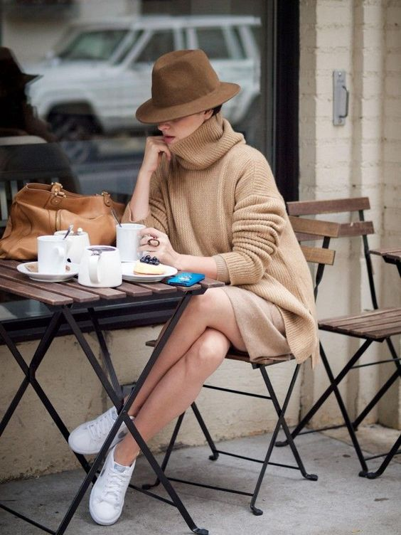 a camel sweater and skirt, a brown hat and white sneakers for a relaxed look