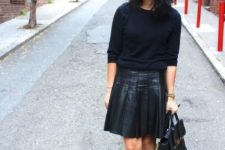 13 a monochromatic outfit with a black top, hat, a leather pleated skirt and nude shoes