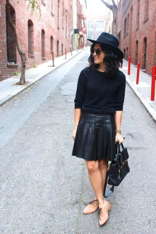 a monochromatic outfit with a black top, hat, a leather pleated skirt and nude shoes