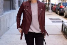 13 black jeans, a grey long sleeve, a burgundy leather jacket and a black bag
