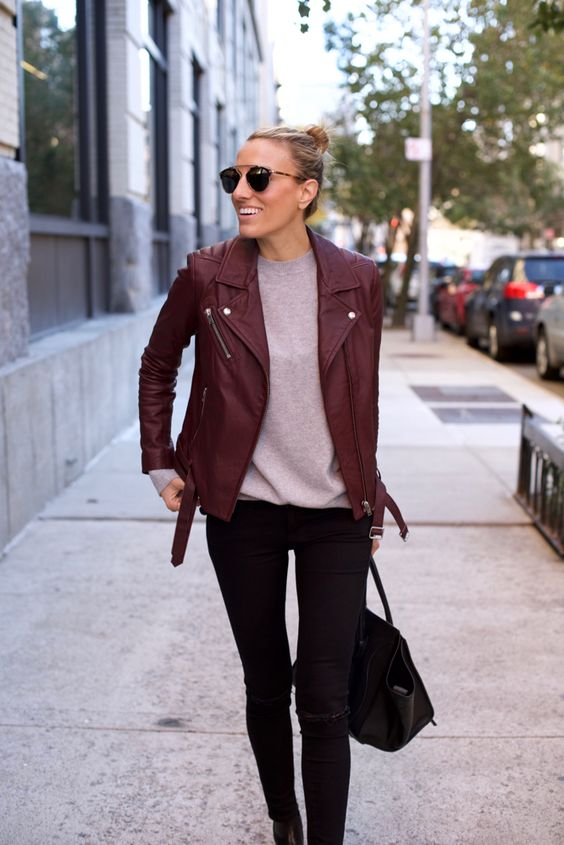 black jeans, a grey long sleeve, a burgundy leather jacket and a black bag