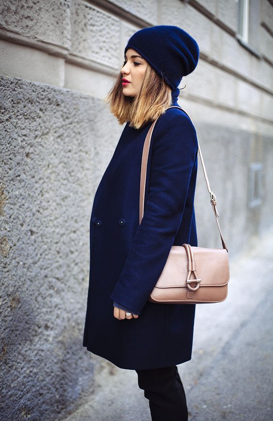 a bold blue coat and beanie, a blush bag and black denim