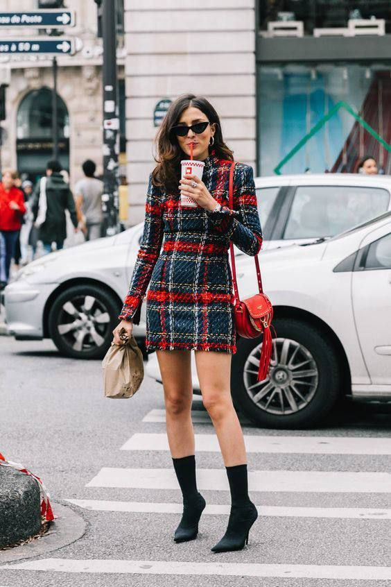 a checked tweed mini dress, a red bag and black sock boots