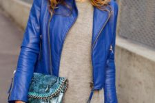 14 black pants, a grey sweater, a bold blue cropped leather jacket and a snake print bag