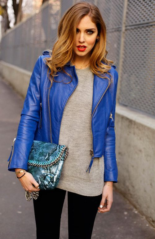 black pants, a grey sweater, a bold blue cropped leather jacket and a snake print bag