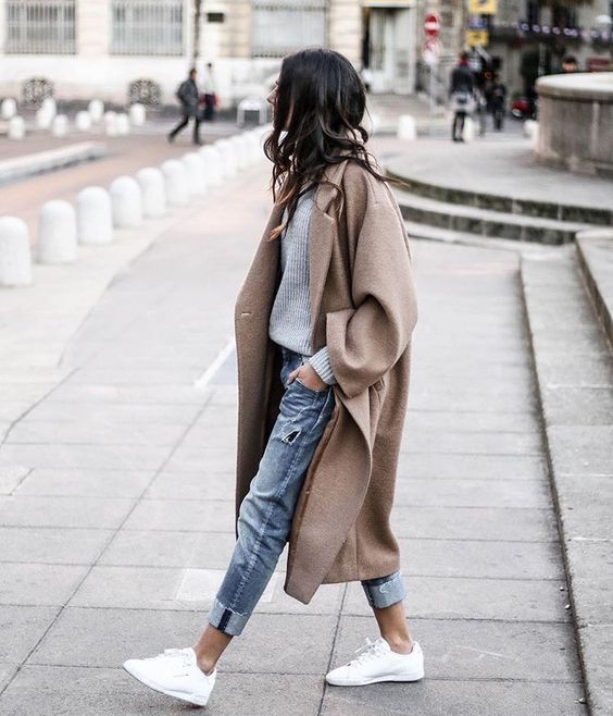 cuffed jeans, a grey sweater, a tan oversized coat and white sneakers