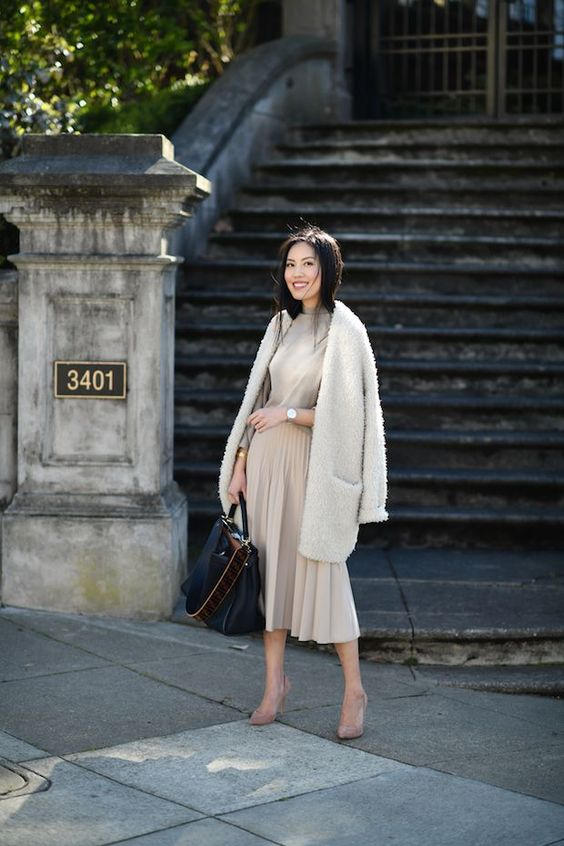 a grey top, an off-white pleated midi, an off-white fluffy cardigan, blush shoes and a bag