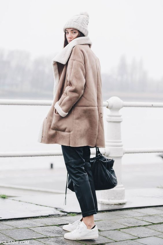 a pompom beanie, black leather pants, a sherpa jacket and white sneakers