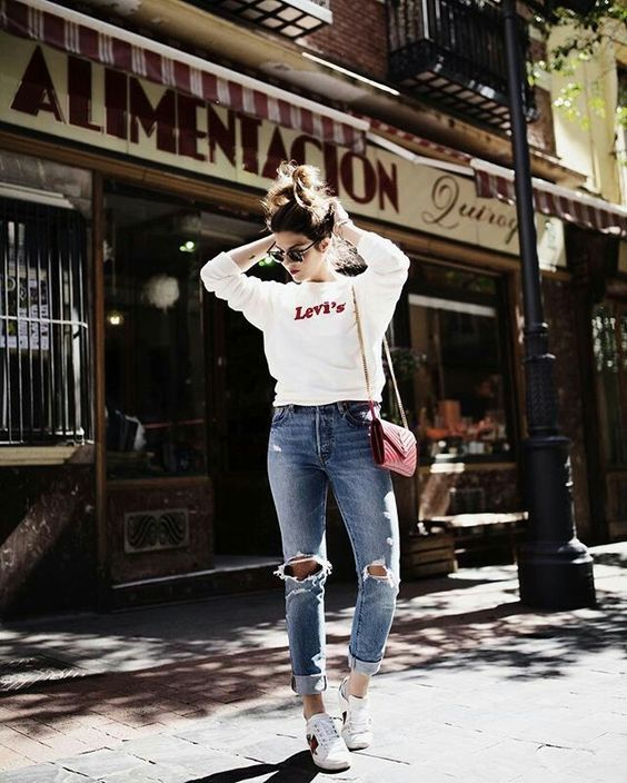a simple white sweatshirt, blue ripped denim, white sneakers and a red bag