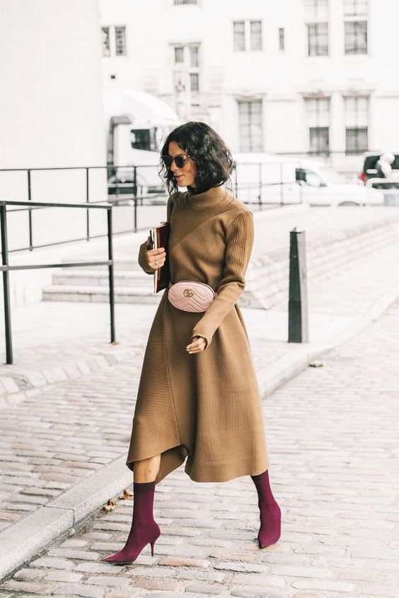 a tan colored midi dress with long sleeves, a blush bag and fuchsia sock boots