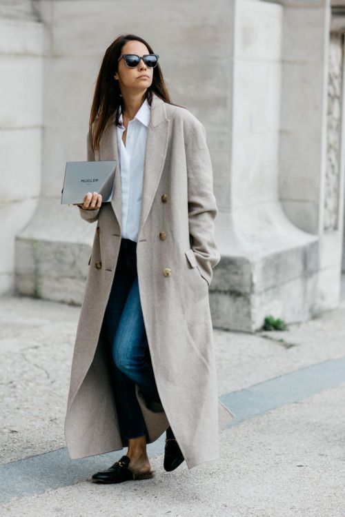 a casual look with a white shirt, blue jeans, black mules and an off white trench