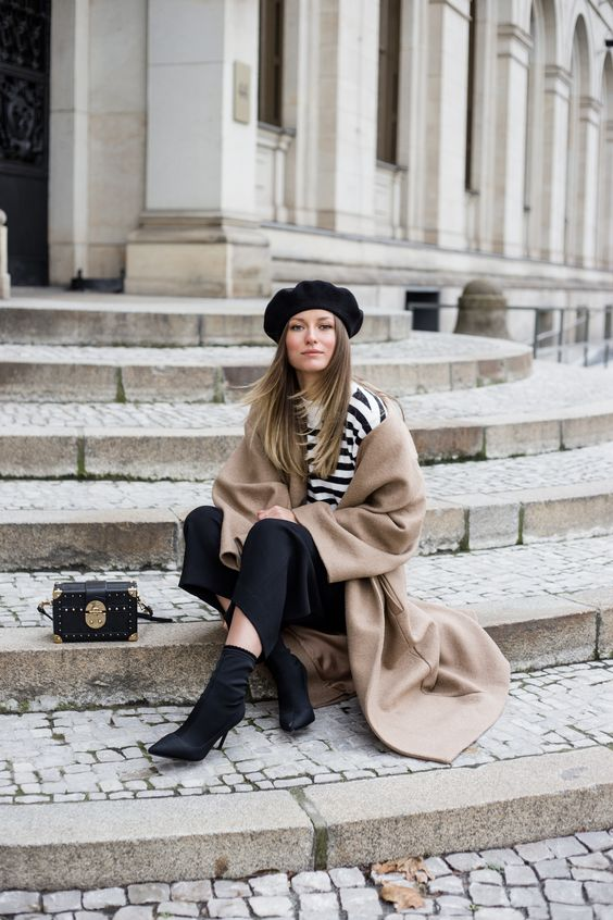 a striped tee, black culottes, a tan coat, black sock boots and a beret hat