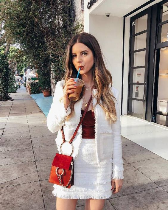 a white fringed suit with a mini skirt, a burgundy velvet top and an orange bag