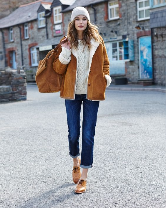 a white sweater, blue denim, an amber shearling coat, amber shoes and a white beanie