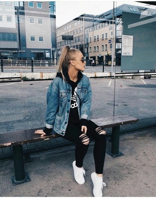 black ripped jeans, a black logo hoodie, a blue denim jacket and white sneakers