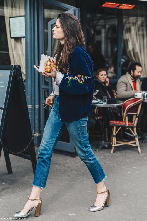 blue raw hem jeans, a navy embroidered bomber jacket, metallic shoes