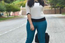 16 teal pants, a white and black top, black shoes and a bag, a statement necklace
