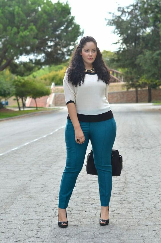 teal pants, a white and black top, black shoes and a bag, a statement necklace