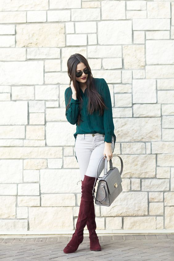 white jeans, plum-colored high boots, a forest grene shirt and a grey bag