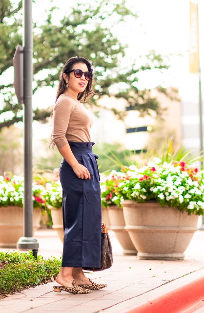 With beige shirt, navy blue culottes and printed bag