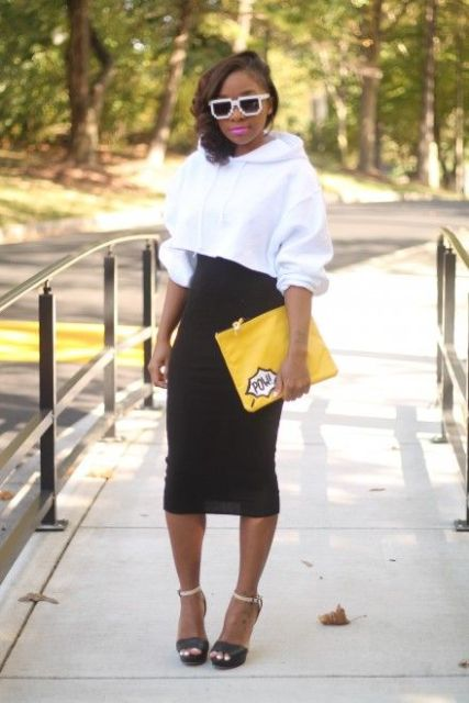 With black high-waisted midi skirt, yellow clutch and two colored shoes