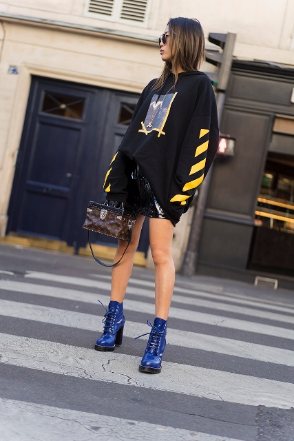 With black leather skirt, blue lace up boots and printed bag