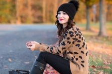 With black pants, pom pom hat and black high boots