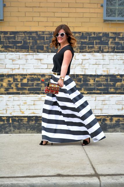 With black shirt, black high heels and printed small clutch
