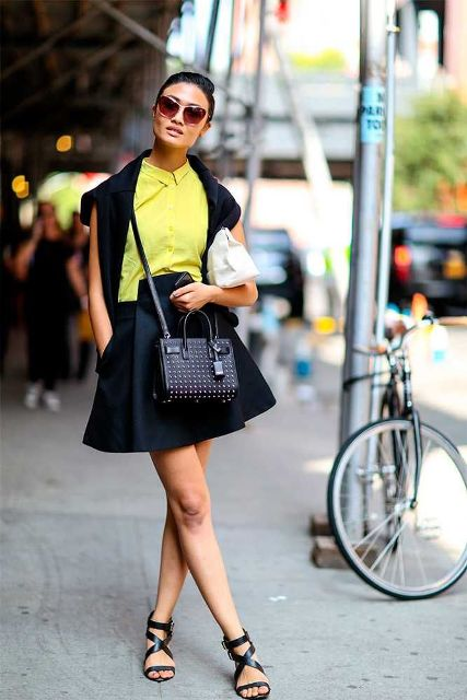 With black sweatshirt, black skater skirt, lace up flat shoes and small bag