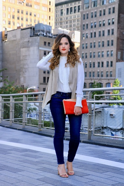 With blouse, skinny jeans, red clutch and beige high heels
