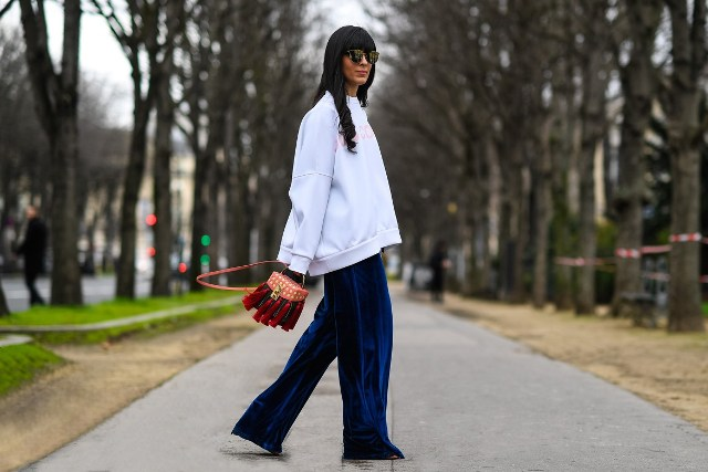 With blue velvet wide leg pants, flat shoes and tassel bag