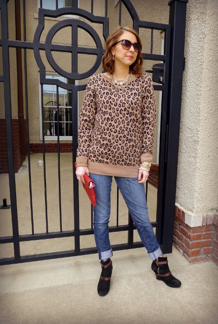 With cuffed jeans, red clutch and brown and black boots
