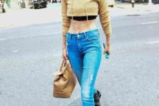 With distressed jeans, black boots and brown bag
