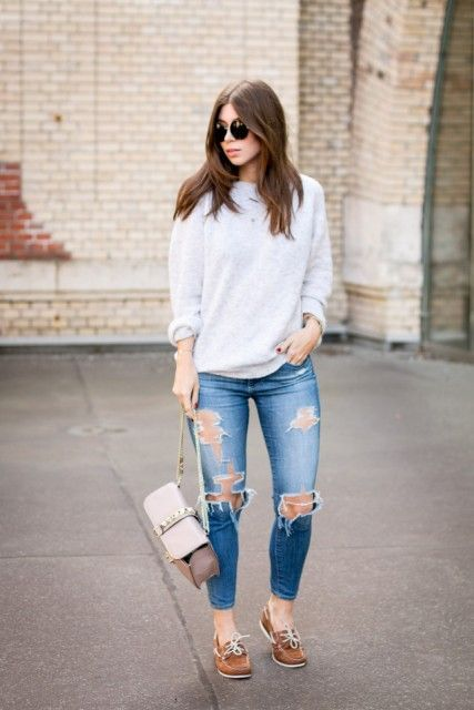 With distressed jeans, brown shoes and beige bag
