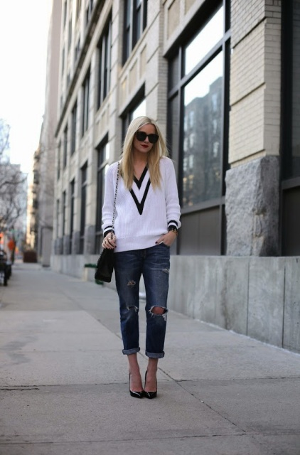 With distressed jeans, chain strap bag and black pumps