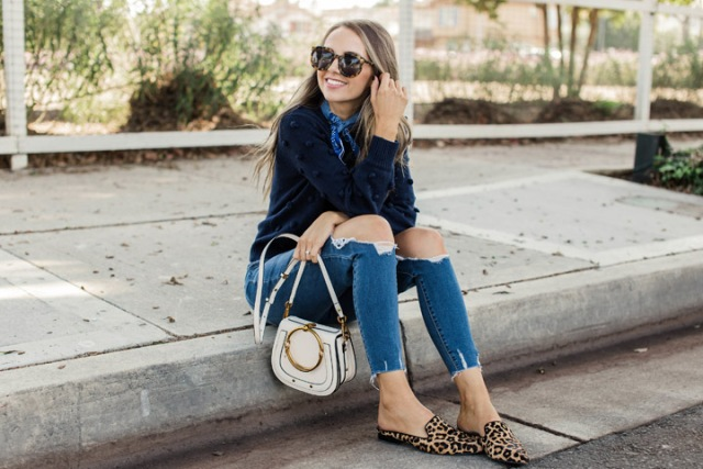 With distressed jeans, white small bag and navy blue sweater