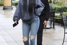 With gray cap, distressed jeans and ankle boots