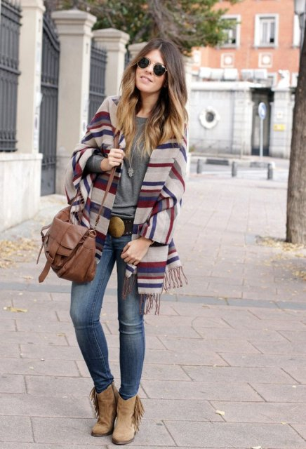 With gray t shirt, skinny jeans, brown bag and fringe boots