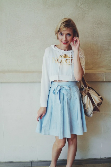 With light blue A-line skirt and beige bag