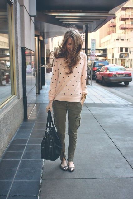 With olive green pants, flats and big bag
