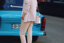 With pale pink blazer, trousers and bag