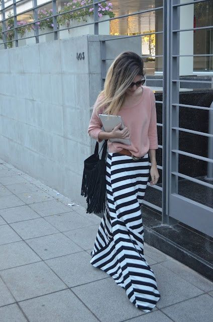 With pale pink loose shirt and black fringe bag