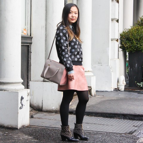 With pink skirt, embellished boots and gray and pink bag