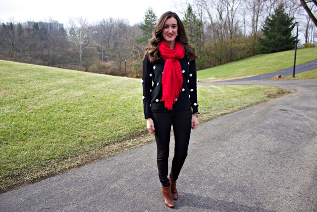 With red oversized scarf, black pants and brown ankle boots