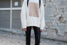 With skinny pants, black backpack and ankle boots