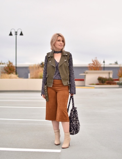With striped shirt, olive green vest, beige ankle boots and leopard bag