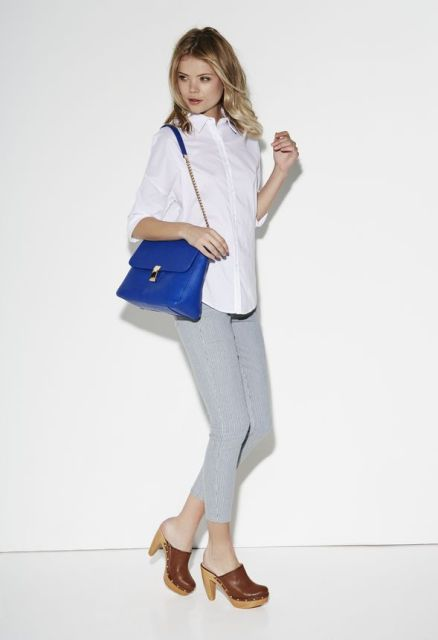 With white button down shirt, gray trousers and blue bag