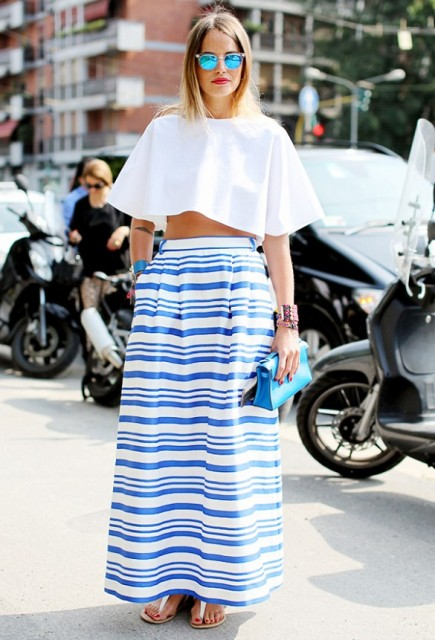 With white crop top, blue clutch and flat sandals
