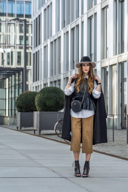With white shirt, leather vest, wide brim hat, black coat and cutout ankle boots