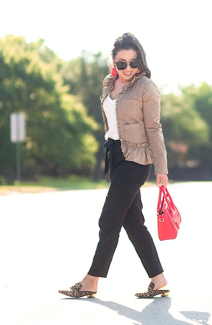 With white shirt, trousers, ruffled jacket and red bag